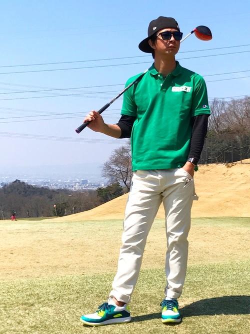 黒キャップ×グリーンポロシャツ×ベージュパンツ