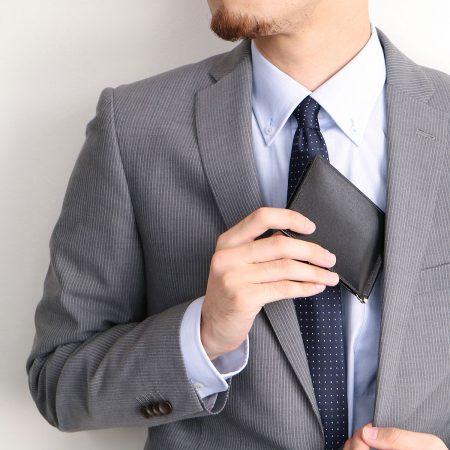スーツから財布を取り出す男性