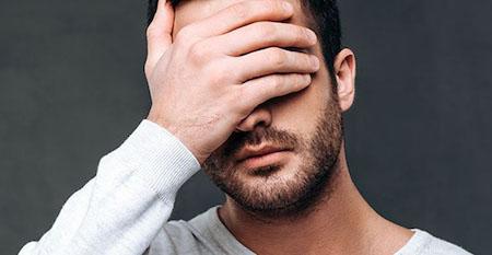 痛みで顔を抑える男性